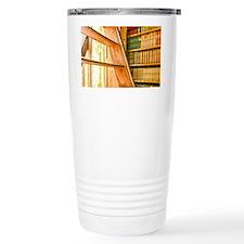 The library contains volumes hu Travel Mug