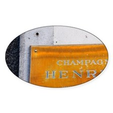 A polished brass sign: Champagne He Decal
