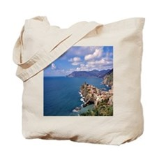 Red-tiled buildings look over the azure w Tote Bag