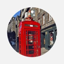 A bright red telephone booth stands Round Ornament