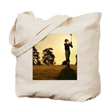 Female golfer swinging club on golf cours Tote Bag