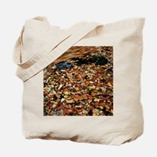 Leaves floating on river water Tote Bag