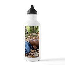 Smiling boy lying on a Water Bottle