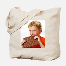 Boy eating chocolate Tote Bag