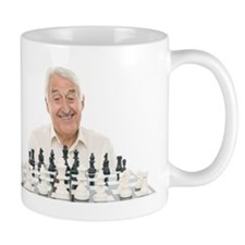 Senior man playing chess Mug