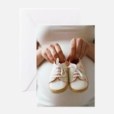 Pregnant woman holding baby shoes Greeting Card