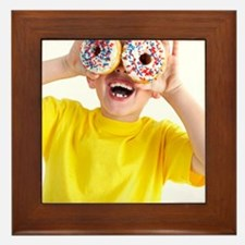 Boy playing with doughnuts Framed Tile
