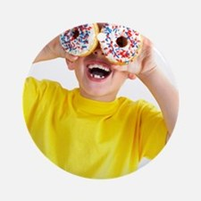 Boy playing with doughnuts Round Ornament