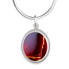 Lava flowing down cliff into  Silver Oval Necklace