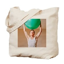 Man Holding Up Fitness Ball Tote Bag