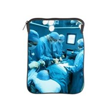 a group of doctors operating on a pati iPad Sleeve