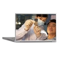 A female dentist holds up a pair of x Laptop Skins