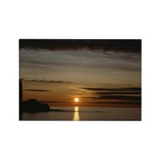 Sun setting over tranquil sea wit Rectangle Magnet
