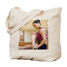 Woman stretching on yoga mat, side view s Tote Bag