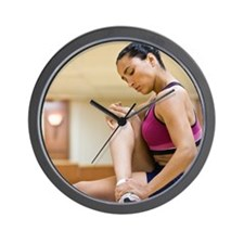 Woman stretching on yoga mat, side view Wall Clock