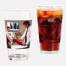Doctor examining full leg cast of p Drinking Glass