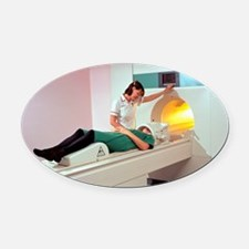A patient is prepared for a MRI br Oval Car Magnet