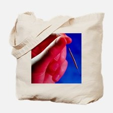 Hand holds a GyneFIX intrauterine contrac Tote Bag