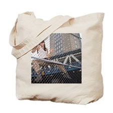 Woman climbing chain link fence Tote Bag