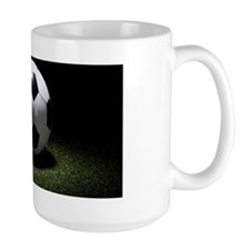A spot lit soccer ball on turf Mug
