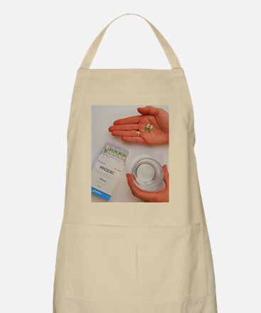 Prozac pack with pills in hand and glass of  Apron