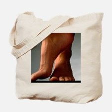 Healthy feet of a woman, raised onto thei Tote Bag