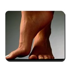 Healthy feet of a woman, raised onto the Mousepad
