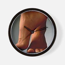 Healthy feet of a woman, raised onto th Wall Clock