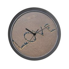 The word Love spelled out in the sand. Wall Clock