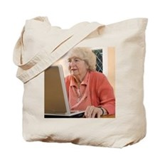 Elderly woman using a laptop computer Tote Bag