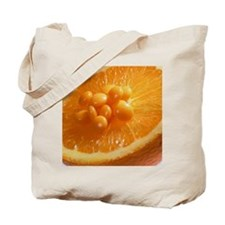 View of vitamin C pills on an orange half Tote Bag