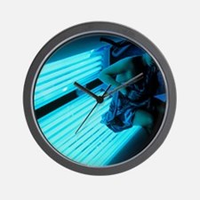 Woman getting off a sunbed Wall Clock