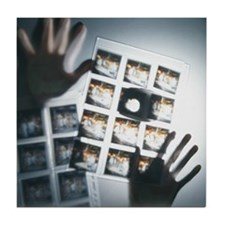 Person with slides on light box, low  Tile Coaster