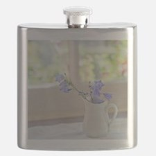 Bell-flowers in small white jug on window. Flask