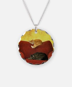 Cats sleeping on sofa. Necklace
