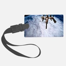 A space station in orbit above t Luggage Tag