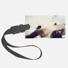 Cat laying on white bed. Luggage Tag
