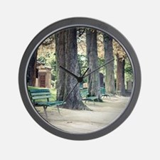 Empty benches lined up with trees in ce Wall Clock