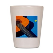 Guitar and its plectrum on a blue table Shot Glass