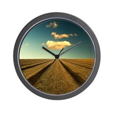 Ploughed field with blue sky and clouds Wall Clock