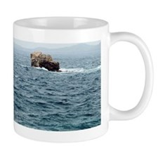 Rock in sea with mountain in background Mug