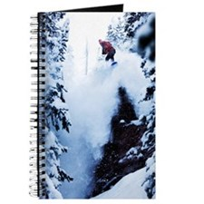 A snowboarder jumping off a cliff in the i Journal