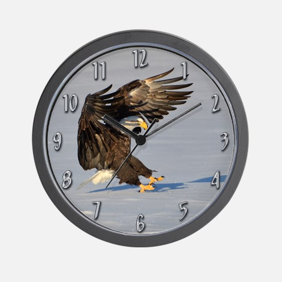 Eagle landing in snow Wall Clock