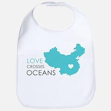 Love Crosses Oceans Bib