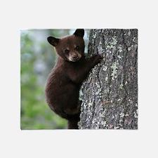 Bear Cub Climbing a Tree Throw Blanket