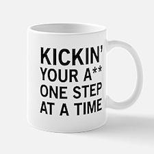 Kickin' a** one step at a time Mugs