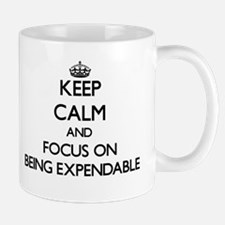 Keep Calm and focus on BEING EXPENDABLE Mugs