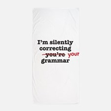 Silently correcting grammar Beach Towel