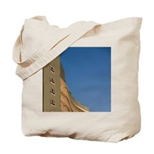 Setting sun lights lighthouse exterior of Tote Bag