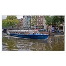 A tour boat full of people travel a canal lined wi Poster